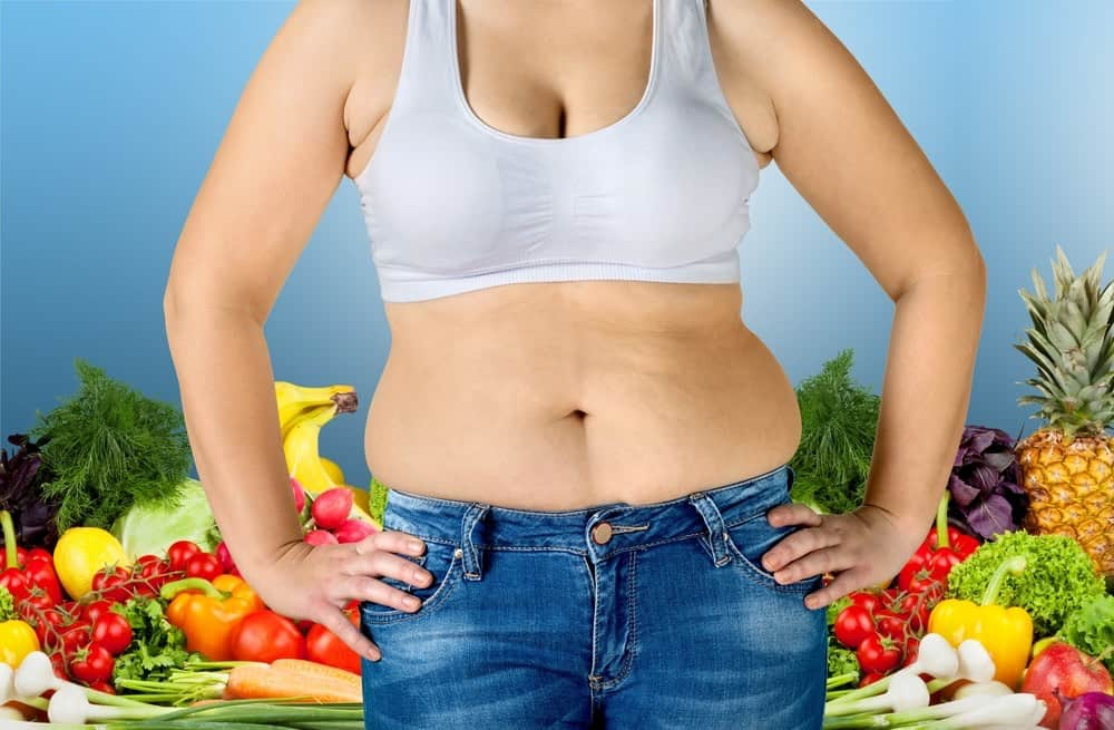 overweight woman standing in front of lots of vegetables