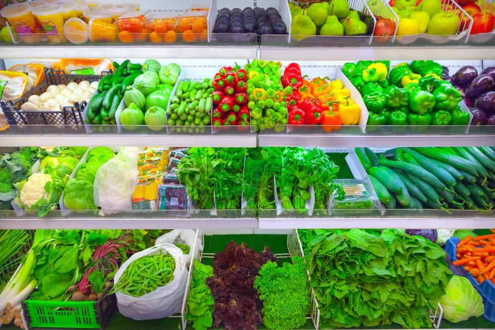 lots of fruit and vegetables on a supermarket shelf