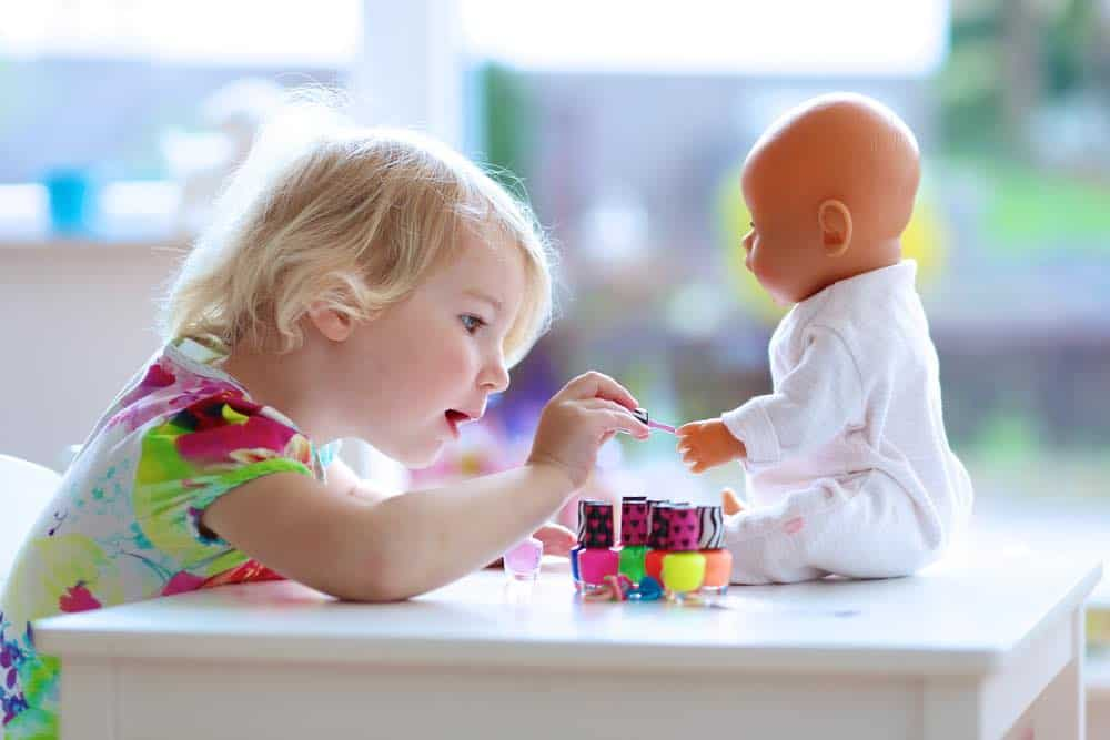 little girl shows how to apply vegan nail polish on a doll