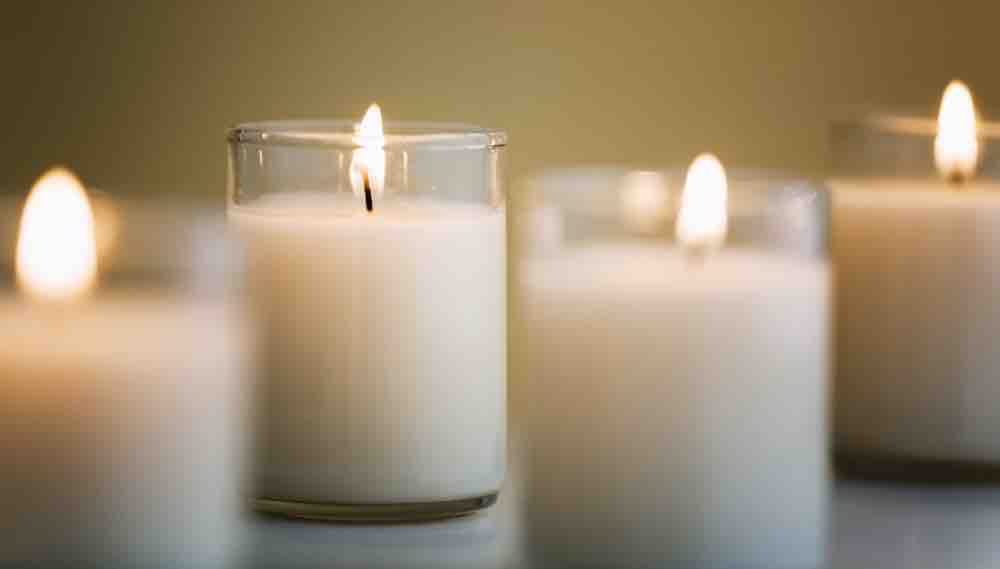 four white candles against a dark background