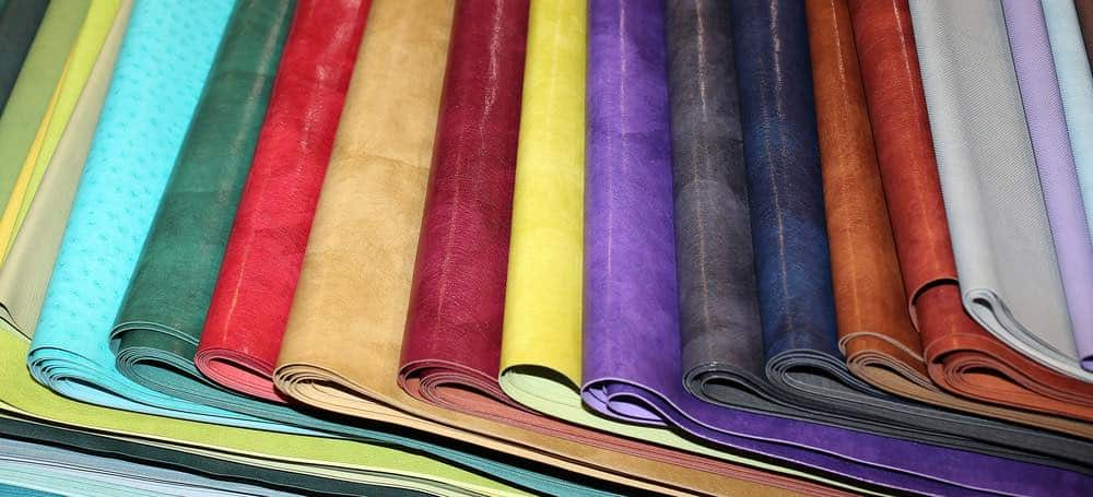 An array of different color faux leather swatches folded and laid out on a table side by side.