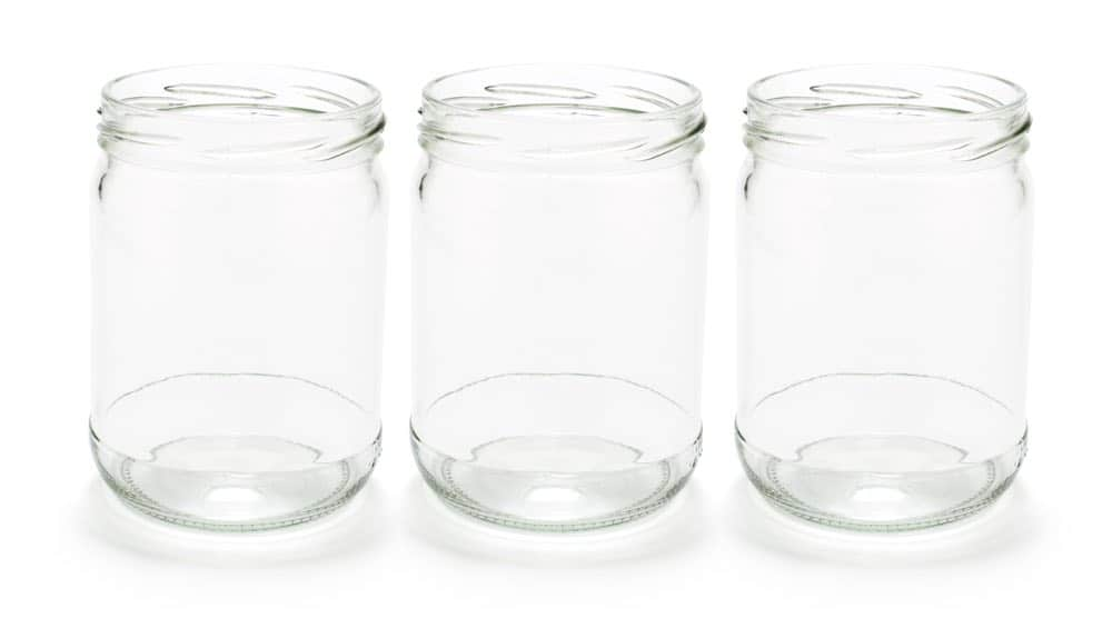 Three empty wide mouth Mason jars without lids against a white background