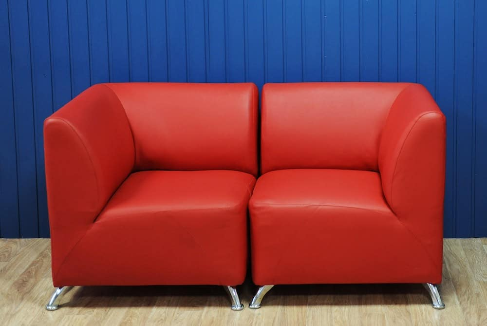 red leatherette sofa against a blue wall on a pale wood floor