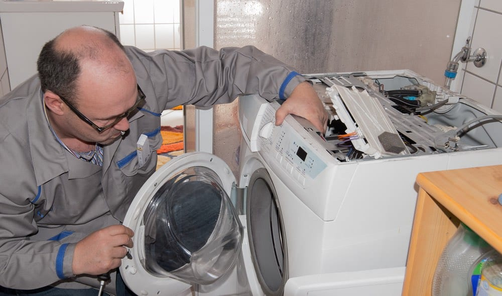 Repairman fixing a front loading washing machine.