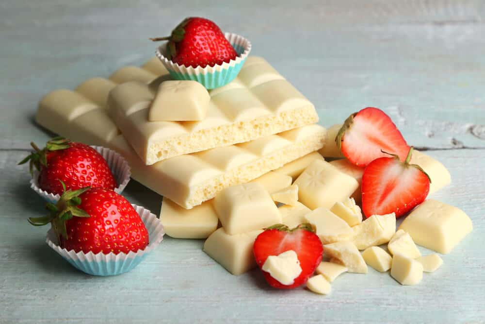 white chocolate bars with squares broken off covered in strawberries on a blue wooden table