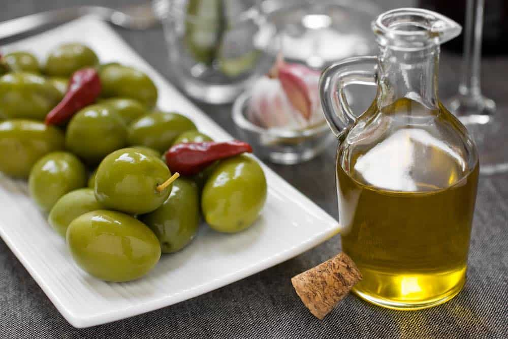 olives on a white plate with a bottle of olive oil on a wooden table