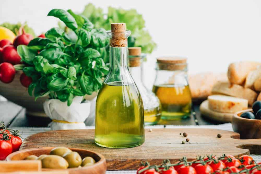 a bottle of olive oil takes center stage amongst various vegetables