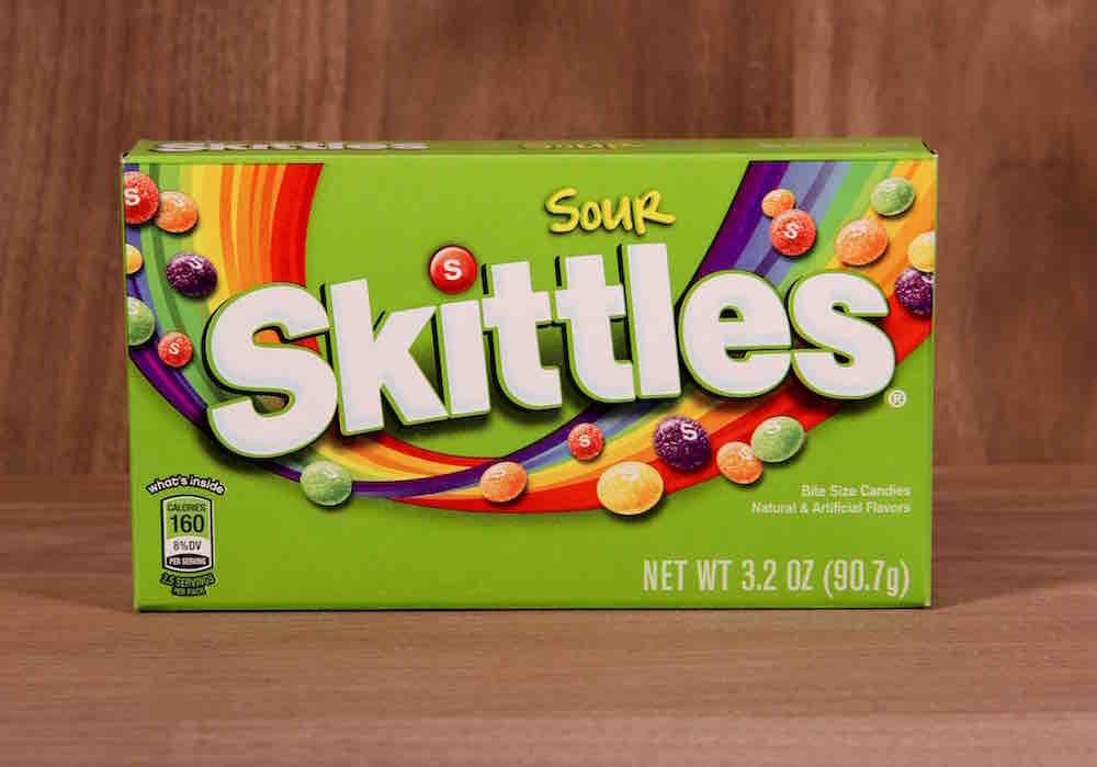 pack of sour skittles against a wooden backdrop
