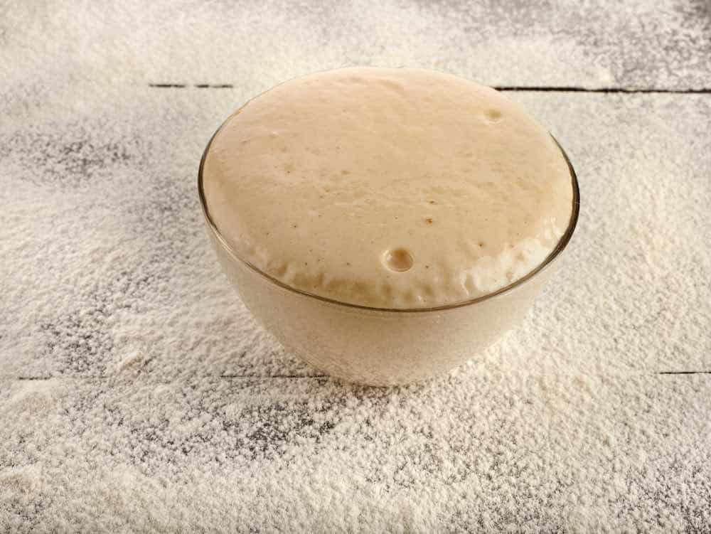 A bowl of bread dough proving on a floured tabletop