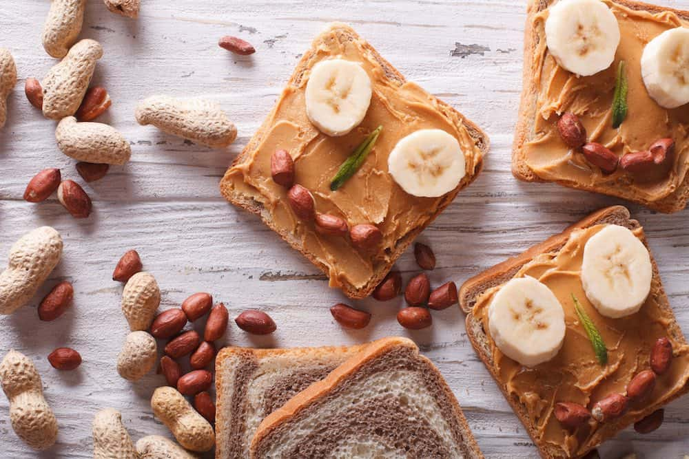vegan peanut butter sandwiches for kids with banana eyes and whole peanuts for mouths atop a wooden table