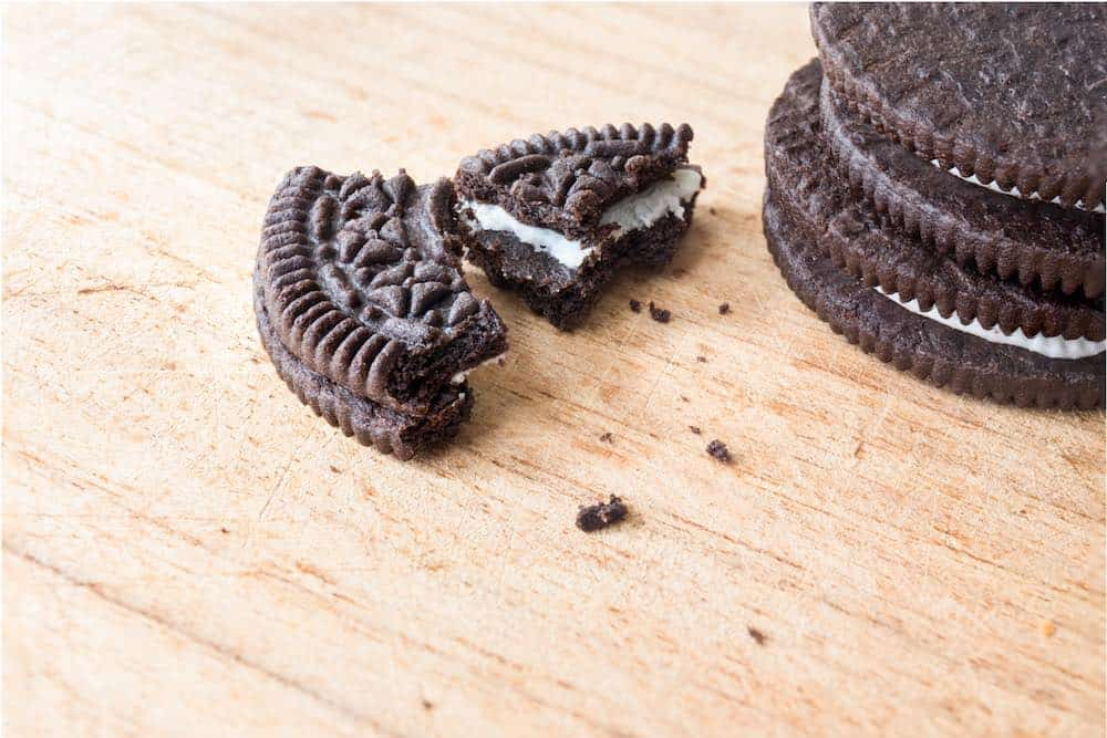 broken piece of oreo near a stack of sandwich cookies on a wooden surface