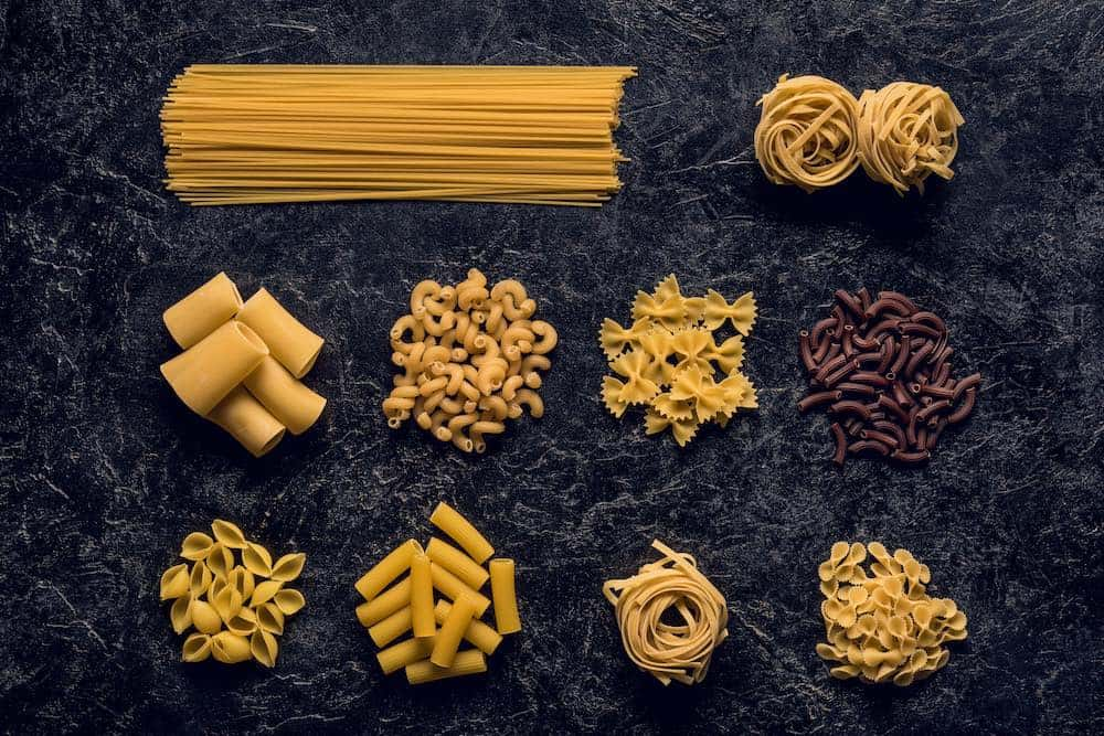different types of dried vegan pasta on a granite slab