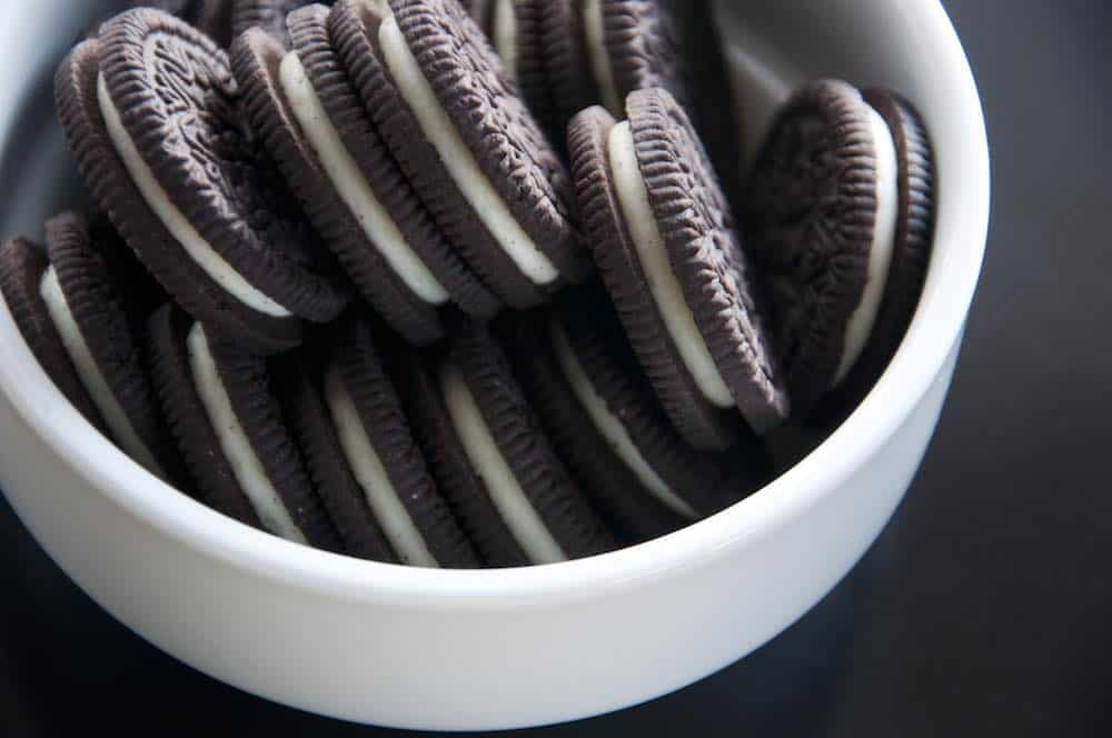 oreo cookies in a white bowl on a gray table