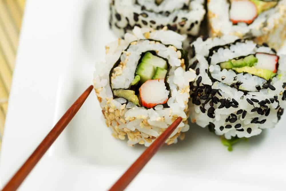 Plate of California rolls with chopsticks looming ready to pick one up