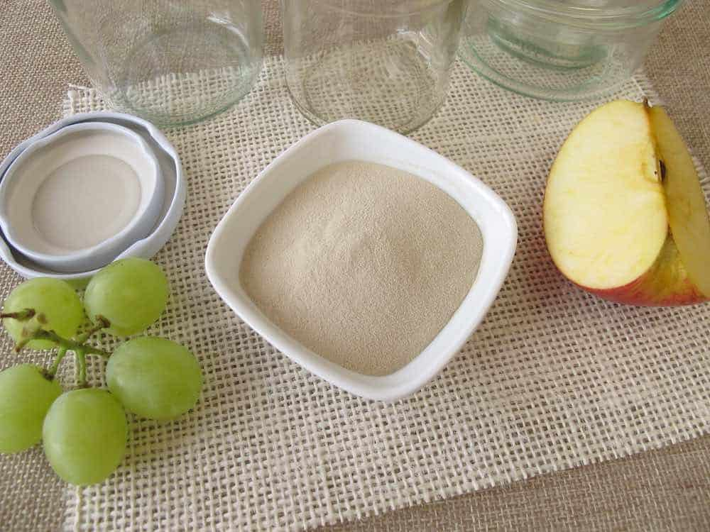 white bowl of agar agar with jars, grapes, and an apple segment on a hessian cloth