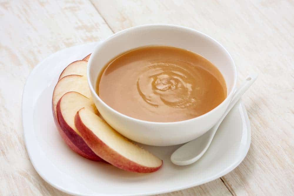 white bowl of caramel sauce with sliced apple and a spoon on the side