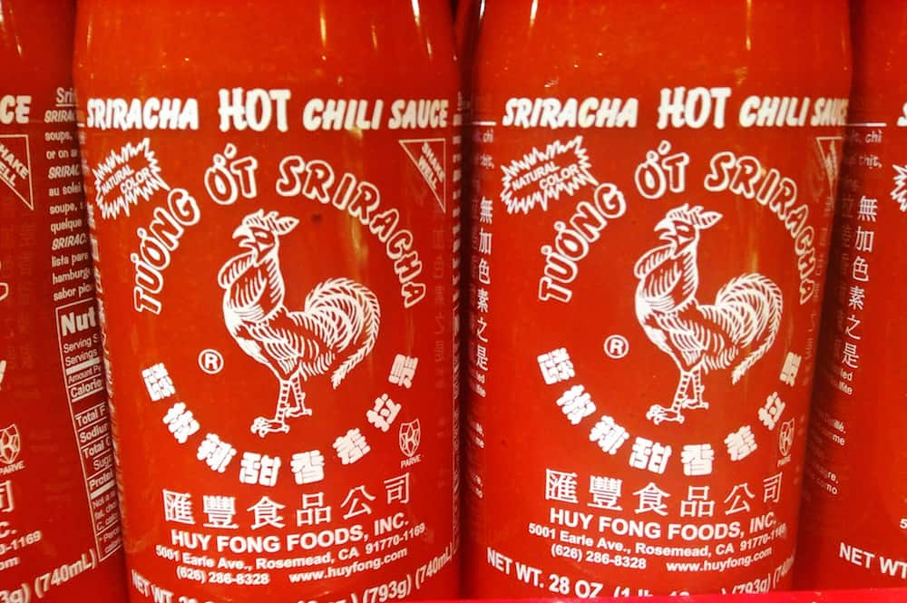 bottles of Sriracha sauce on a shelf