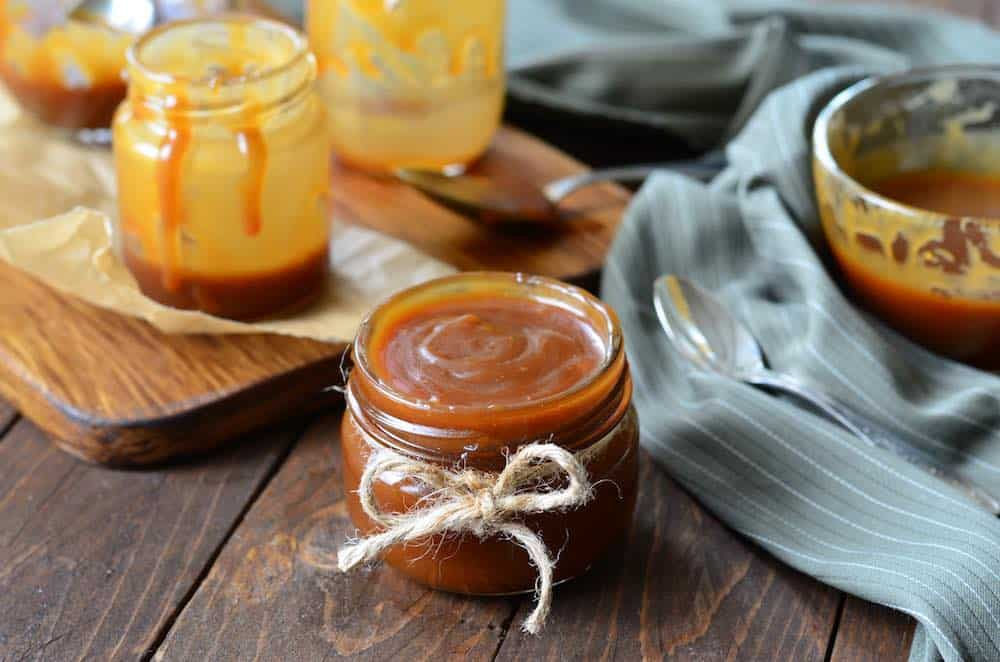 jar of homemade vegan caramel sauce on a wooden table with blue napkins, spoons, and other jars