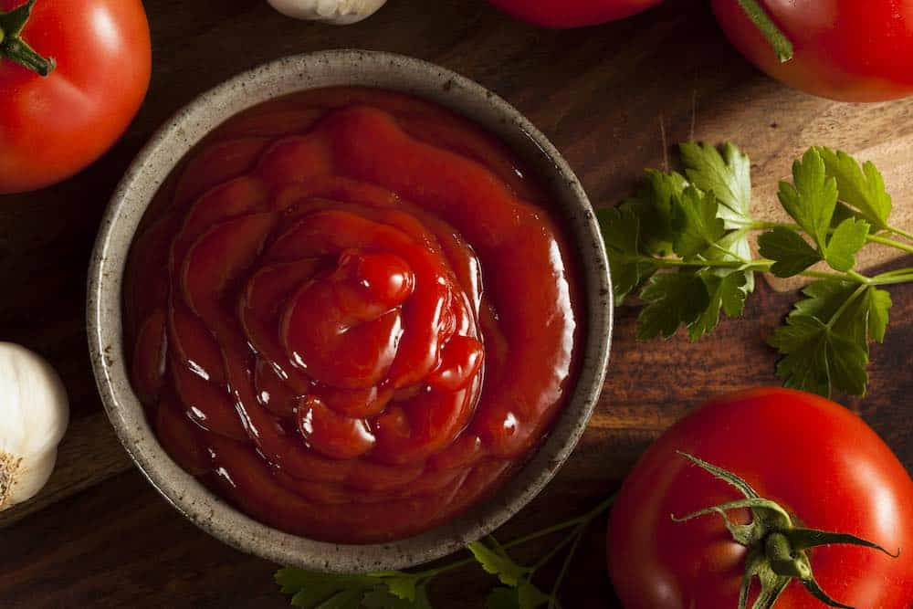 tomato sauce ketchup in a ceramic bowl with garlic and herbs on a wooden table
