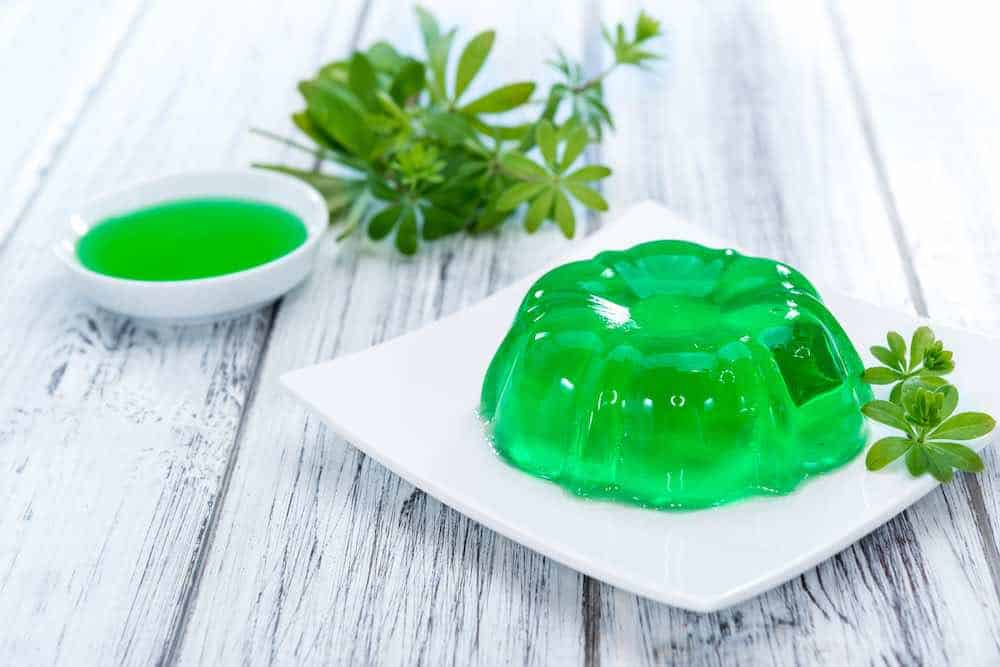 green jello pudding, vegan friendly, on a white plate placed on a white oak table