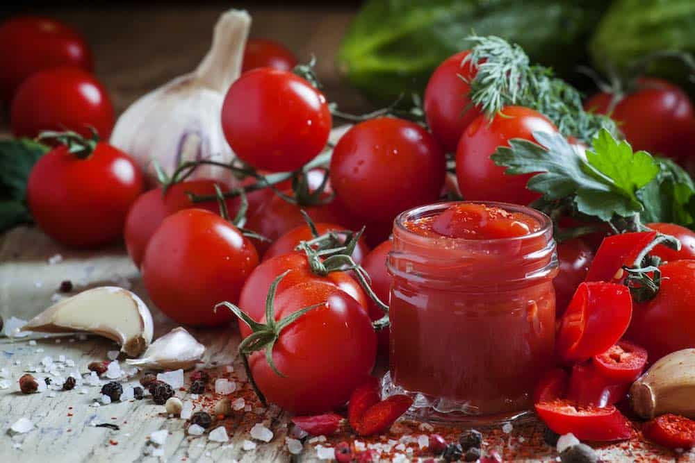 jar of tomato ketchup surrounded by ingredients such as garlic, chili, salt, pepper, basil and other herbs