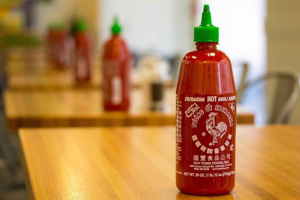 Sriracha sauce on adjacent tables in a diner