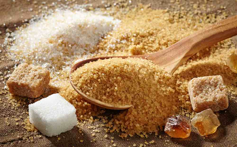 different types of sugar on a wooden table