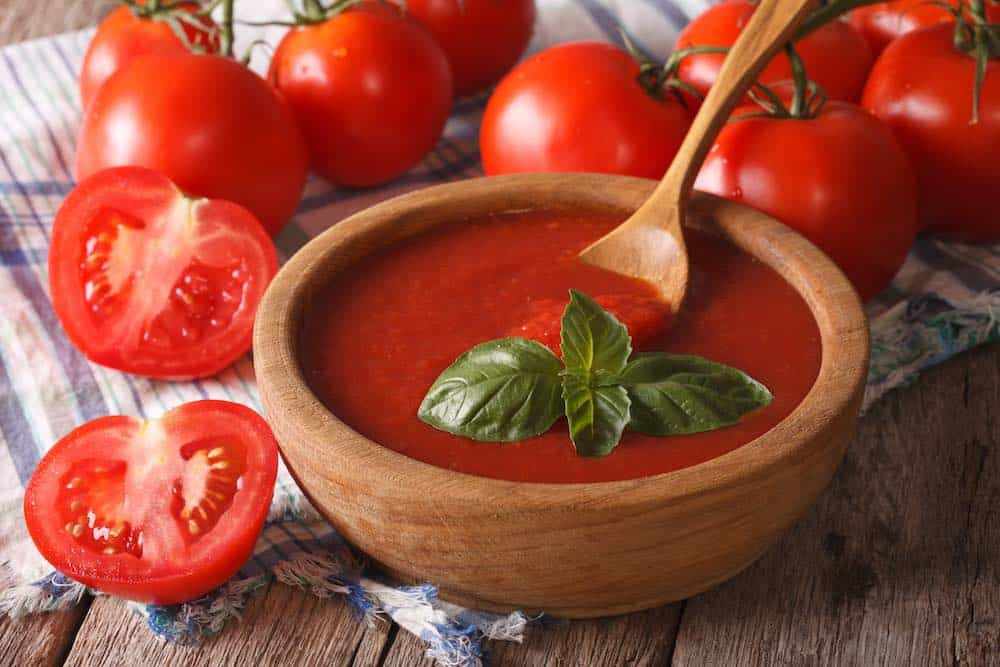 wooden bowl of tomato ketchup surrounded by tomatoes with a sprig of basil and a wooden spoon upon a check napkin on a table