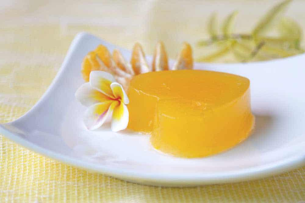 orange vegan jello heart on a white plate with flowers