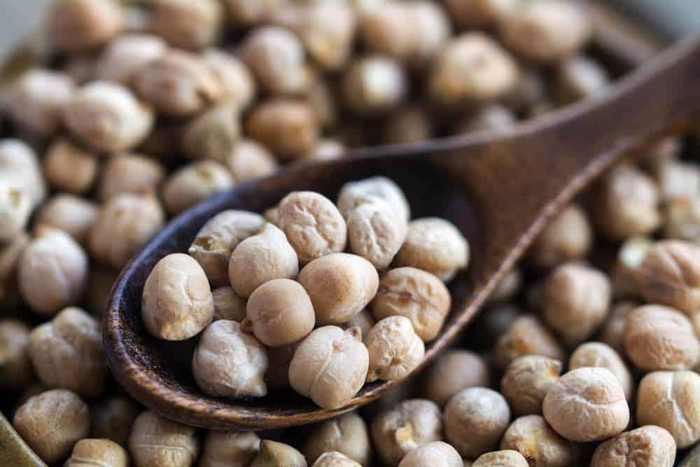 close up of chickpeas on a wooden spoon above a bowl
