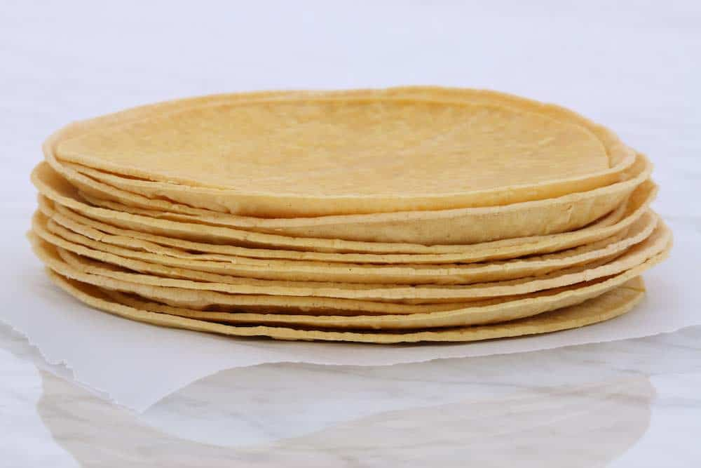 stack of corn tortillas on a sheet of baking paper