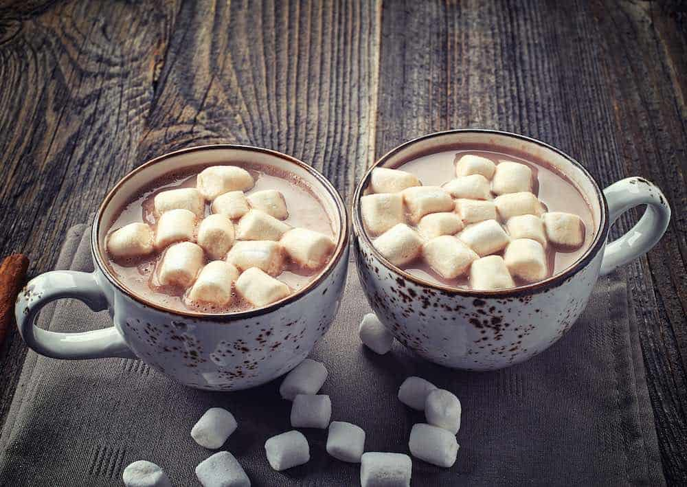 two cups of hot chocolate with vegan marshmallows on top and scattered around on a wooden table