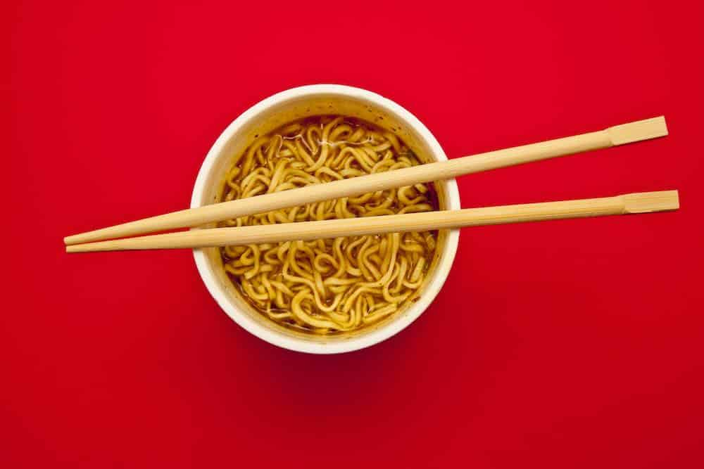 Pot of instant noodles with chopsticks resting on top standing on a red table and photographed from above