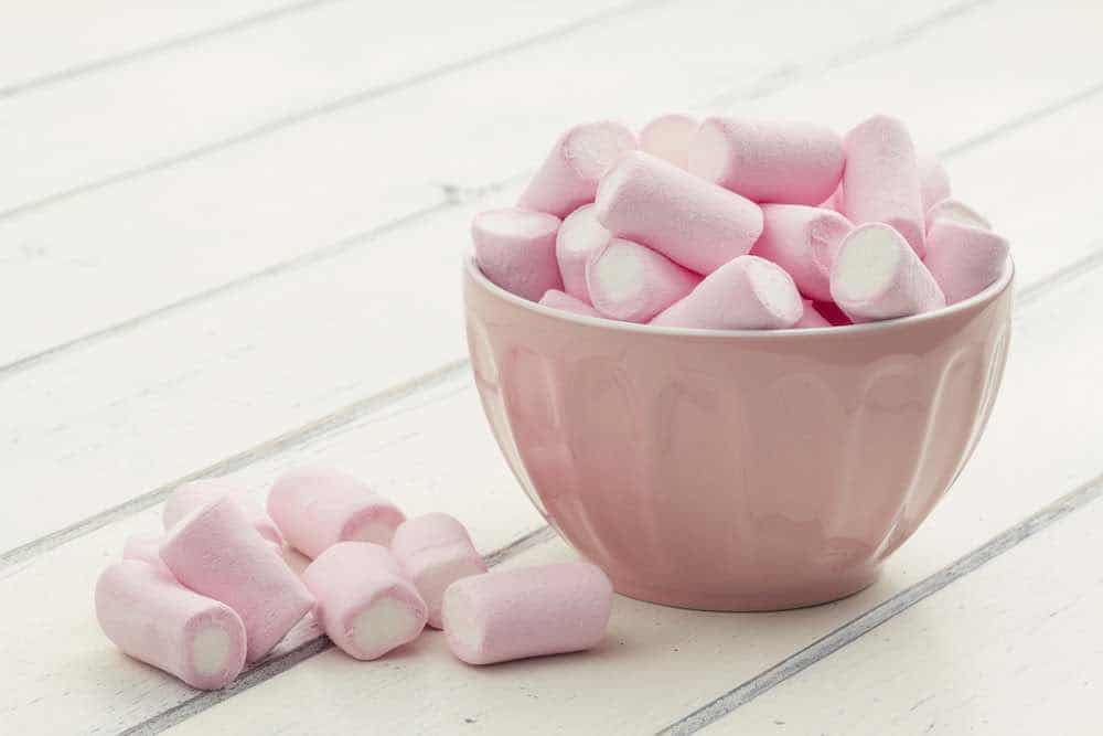 pink bowl full of vegan marshmallows on a white wooden table