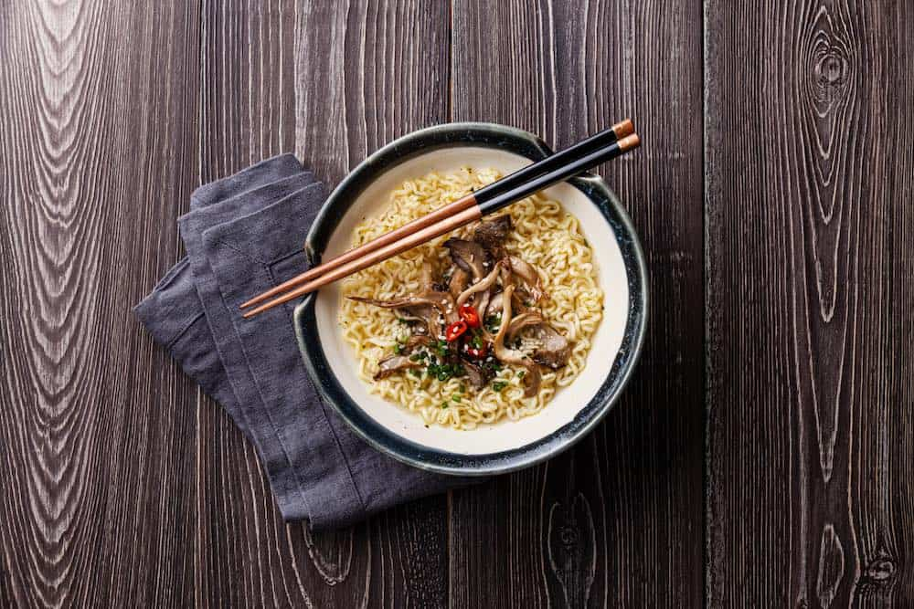 bowl of vegan ramen with chopsticks on a dark wood table