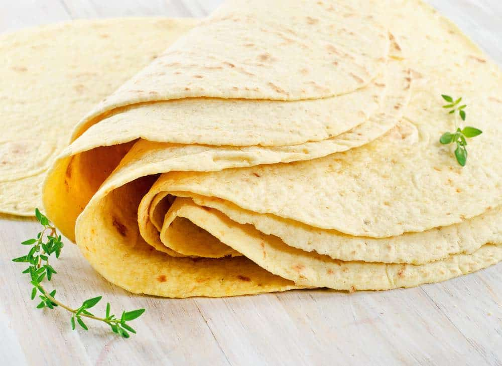pile of folded vegan tortillas on a white wood table