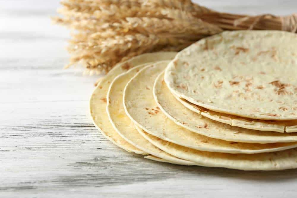flour tortillas with ears of wheat on a marble surface