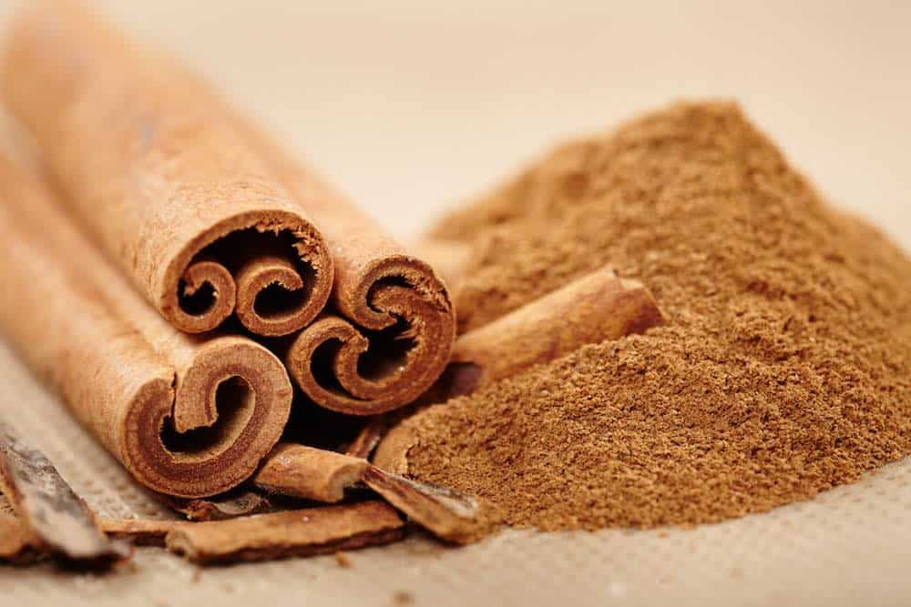 how to buy cinnamon - sticks, ground on a wooden surface