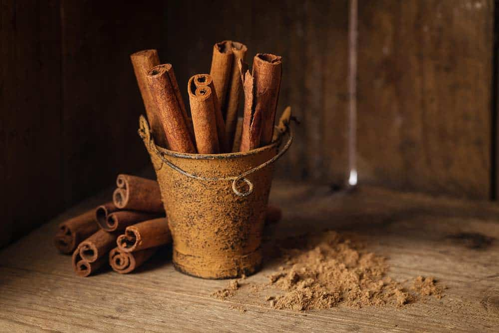 bucket of cinnamon sticks with ground spice next to it