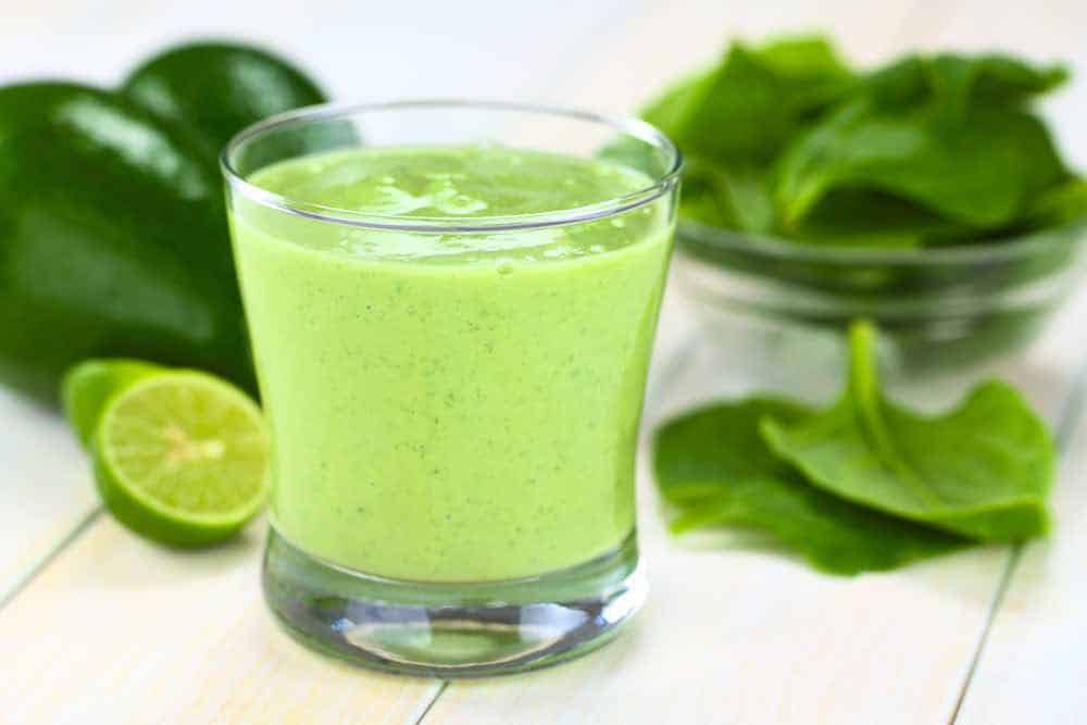 spinach smoothie with raw leaves and limes in the background