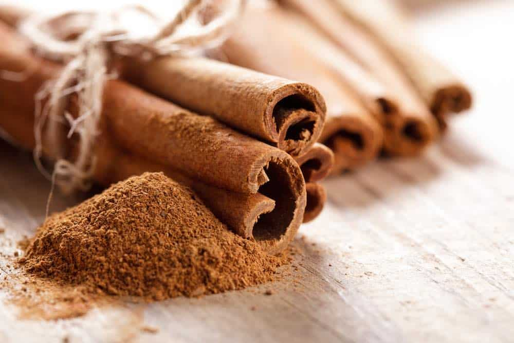 cinnamon 101 guide to spice - tied sticks and powder on a table