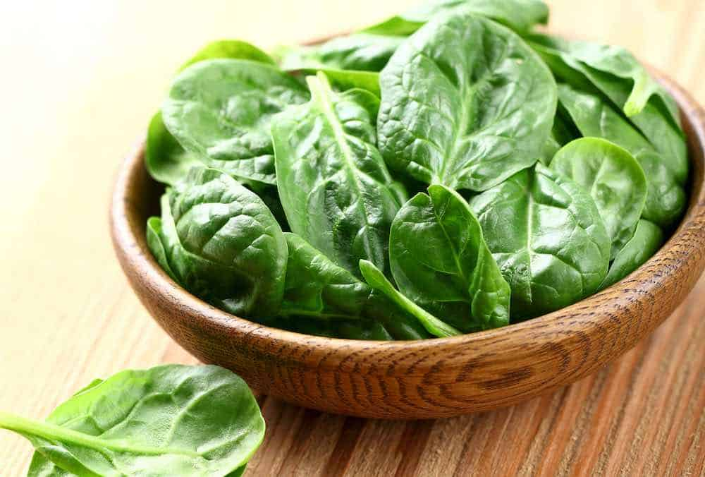 wooden bowl of green spinach