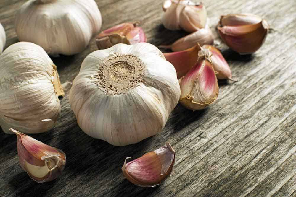 how to buy garlic - bulbs and cloves on a wooden table