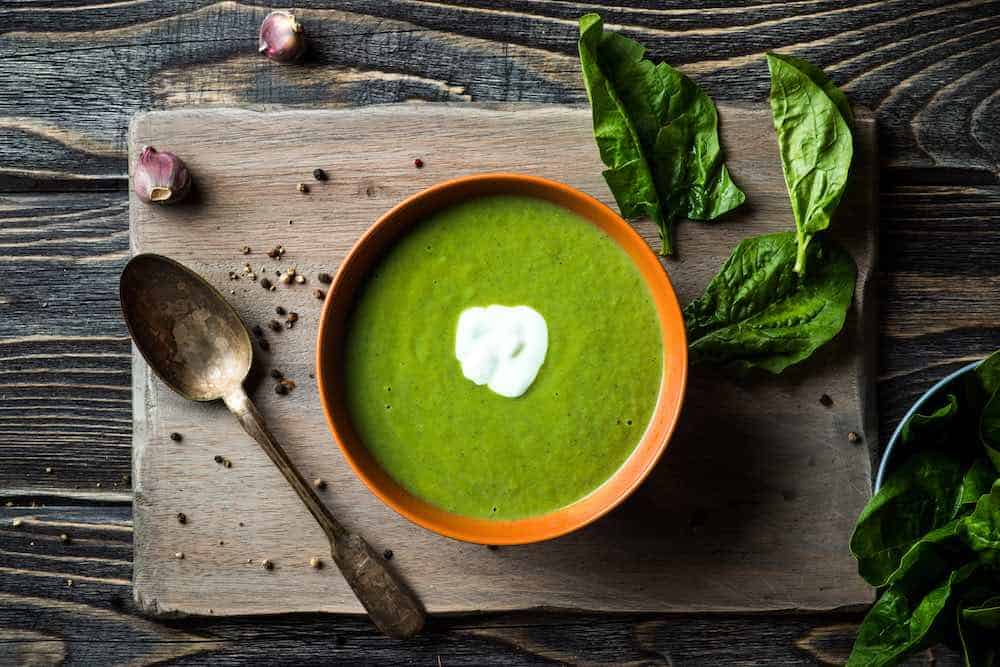 bowl of fresh spinach soup on a board with spoon, peppercorns, and raw spinach leaves