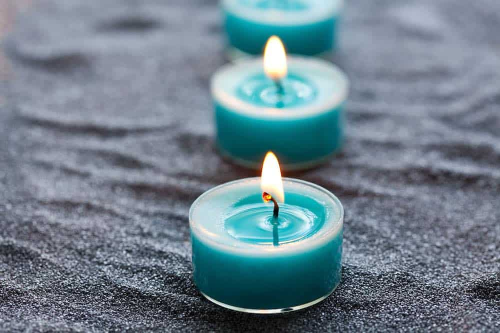 three blue soy candles in a line
