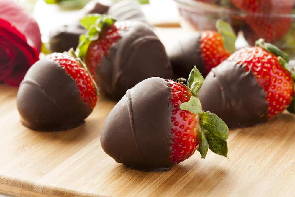 chocolate covered strawberries on a wooden board
