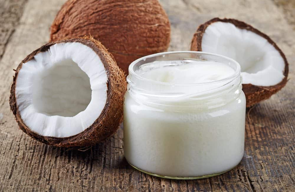 coconut whole and halved with a jar of oil in front