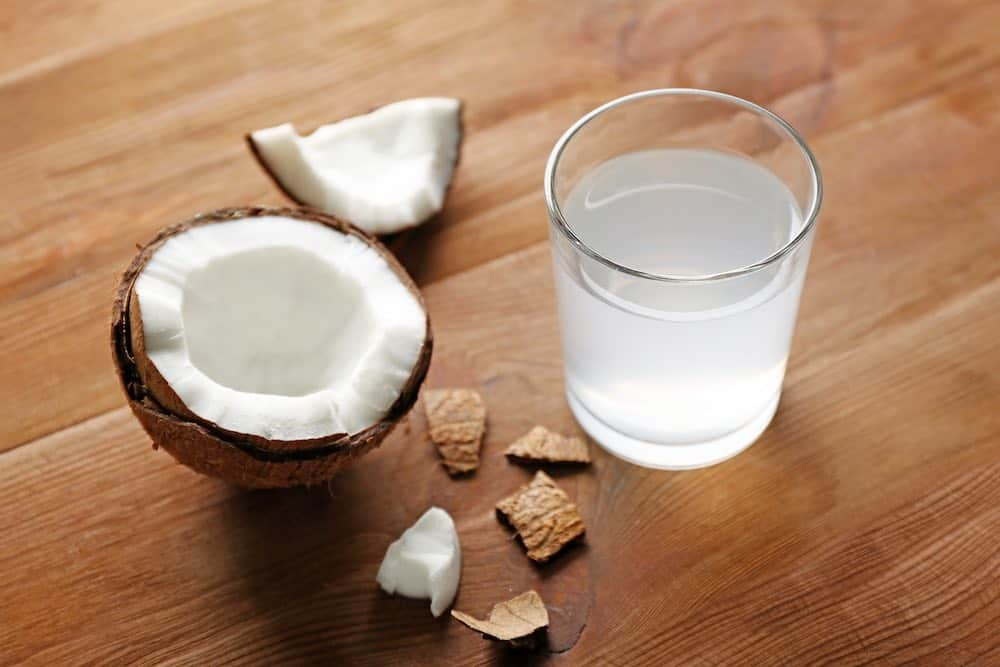 opened coconut with a glass of its water