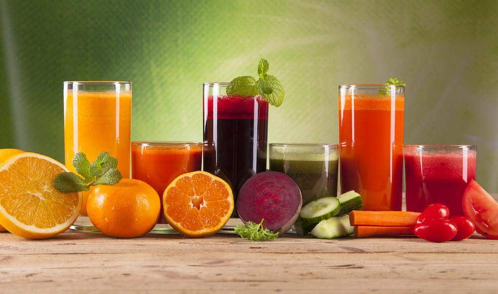 can ninja juicer - different types of fruit juices against a green background