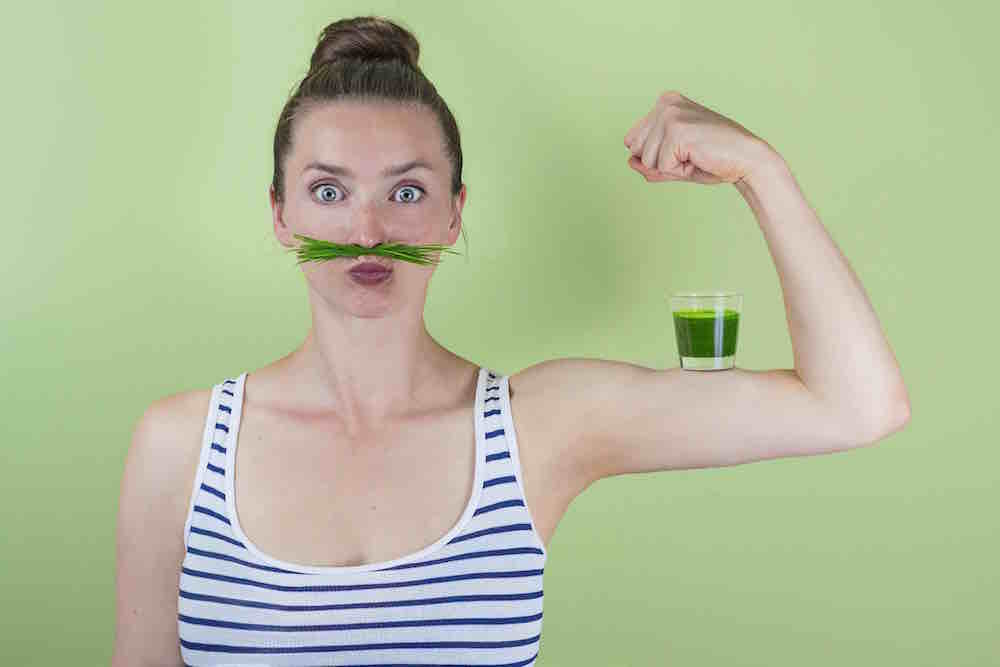 woman in a striped top with a wheatgrass moustache and a glass of green juice on her bicep